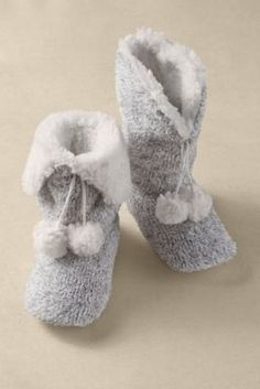 Plush and fluffy, faux fur lines these snuggly soft slippers, hand-knit in tweedy, textural yarn and detailed with an adorably floppy pompom. Ultra-cushy padded footbed delive