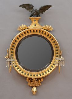 REGENCY GILTWOOD AND EBONIZED CONVEX MIRROR  The round mirror plate within an ebonized border and deep frame decorated with balls, surmounted by an eagle on a plinth, the sides fitted with scrolling candle branches and terminating in pod finial. 44 x 27 1/2 in. Decor Interior Design, Interior Design Living Room, Living Room Designs, Interior Decorating, Mirror Plates, Round Mirrors, Antique Mirrors, Mirror Photo Frames, Wall Mirror