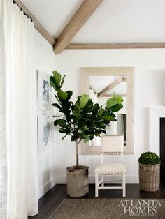 Chic living room features wood beams over a distressed beveled wall mirror lined with a cream nailhead chair and a potted fiddle leaf fig plant. Coastal Bedrooms, Coastal Living Rooms, Chic Living Room, Living Room Decor, Coastal Curtains, Coastal Bedding, Style Cape Cod, Home Interior, Interior Design