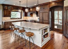I kinda like this for a cozy feel. Notice: Cabinets not quite so dark or cherry Island is white Wonder: How would lighter tile floor look? Other lighting over island-chandelier? White pantry door instead of dark? Where does color come in?