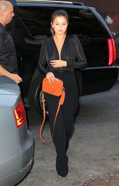 AQ/AQ Cray Ruched Bodysuit in Black,  L'Agence black Wide Leg Trousers, Saint Laurent Classic Paris 110 Chelsea 110 Ankle Boots in Black leather, Gucci Soho Disco Bag in Orange Suede.