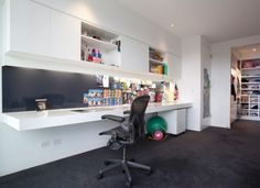 This home office has lots of storage. IT features a floating white desk and a long wall unit hanging above it that includes shelves and storage compartments for anything from books to office supplies. In front of the desk there's a magnetic wall with glass on top. It's a very interesting idea that can be applied to other spaces as well.