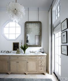 Custom-made cabinetry, sink fittings by Rohl, and a silver-leafed mirror by Eloquence in the master bath; the chandelier is Venetian glass.