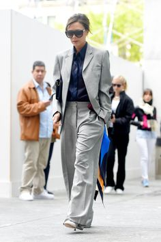 Victoria Beckham walks through the streets of New York in a matching grey suit with a buttoned-up blue shirt, May 2017 #victoriabeckham