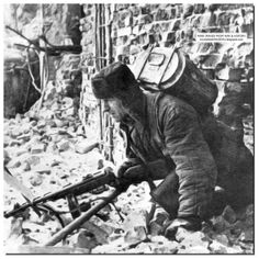 """Stalingrad, 1942/43, This Russian performs a very vital duty. Gun in hand and a food tiffin on his back the man crawls through the ruins of Stalingrad to give food to the Soviet soldiers fighting at the """"front line"""""""