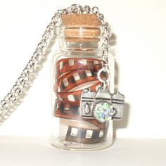 Camera necklace, with a curled strip from a vintage photograph negative in a little glass bottle $21.51