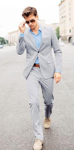 Acheter la tenue sur Lookastic: https://lookastic.fr/mode-homme/tenues/costume--bottines-chukka-ceinture-lunettes-de-soleil/3147 — Chemise à manches longues bleu clair — Costume gris — Ceinture en cuir brun — Lunettes de soleil brun foncé — Bottines chukka en daim beiges