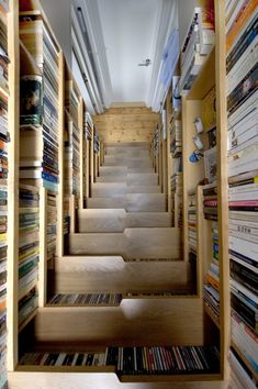 """Book-lined staircase"" -- London-based Levitate Architects came up with this ingenious solution to a book storage problem and created a loft-like bedroom nestled under the roof of the top-floor apartment. (text from the original website)"