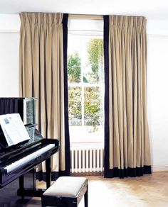 Jute curtains with triple pleat heading and leading edge and bottom borders in Como Chocolate hung on a lath & fascia