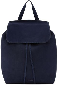 Unstructured suede backpack in 'blu' navy. Carry handle at top. Twin adjustable shoulder straps featuring strap pads. Logo stamp in gold-tone at face. Foldover flap with tab-slot fastening. Drawstring at throat. Zippered pocket at raw interior in black. Gold-tone hardware. Tonal stitching. Approx. 10.5