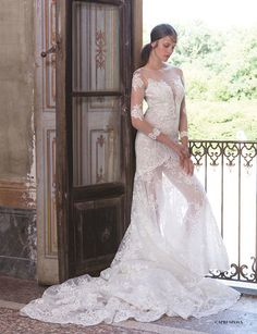 A translucent cathedral lace trail ends in the brocade bodice with a deep v-neck. Delicate 3/4 sleeves and boat neckline give the dress a strictness and sensibility that is dispelled by the translucent fabric of the skirt. A graceful and bold choice for the special day   Capri Sposa   Fall/Winter 2015/16