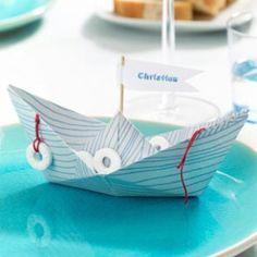 Frische Brise für Ihre Tafel: Mit diesen Platzkarten sorgen Sie im Handumdrehen für maritimes Urlaubs-Flair! Wir erklären Schritt für Schritt, wie Sie aus schönem Papier ein Papierboot falten.