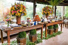 A mesa de doces foi atração no casamento. Decoração com flores coloridas, folhagem e buxinhos.