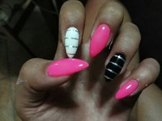 Unghie a stiletto rosa neon con anulare bianco e medio nero con striping argento
