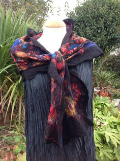 A beautiful nuno felted silk scarf with a base of printed silk georgette that has a red background and blue, gold and beige highlights in the pattern. I have felted this with blue, black and red fine merino wool fibre with some hints of a goldy yellow too. The silk has felted and ruched