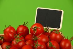 Fresh cherry tomatoes with black chalkboard sign over green background Agriculture Blackboard  Chalk Chalkboard Cherry Tomatoes Close-up Concept Food Food And Drink For Sale Freshness Green Background Harvest Healthy Eating Market Nature Organic Price Tag Red Retail  Season  Sign Studio Shot Tomato Vegetable