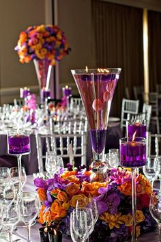 Some tables have low floral centerpiece (only purple and white flowers) with large vase of water in center (large white candle floating)- cylindrical vase though to match other table centerpieces.