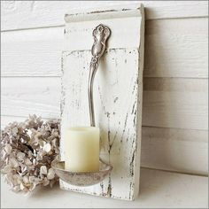 Silver spoon soup ladle pinned on wood as a candle holder
