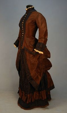 1883 extant gown -copper brown silk, contrasting striped fabric trim, vest insert also of striped fabric, brown piping on edges