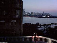 A woman looks on at the vast skyline ahead of her as she stands on a balcony. With a light illuminating her from the front, she appears to radiate in the darkness of the run-down building beside her.