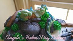 Baby in a dragon costume cake topper. Bsby shower cake.