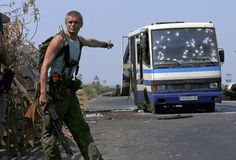 An armed pro-Russian separatist points at a bus riddled with bullet holes at a checkpoint on the outskirts of Donetsk, Ukraine, August 13, 2014. REUTERS/Sergei Karpukhin http://blogs.reuters.com/fullfocus/2014/08/13/editors-choice-53/#a=6