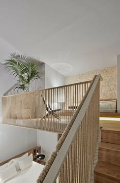 modern mezzanine room design with hemp rope railing, wooden interior staircase, limestone wall and w