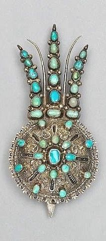 A turquoise-set silver turban pin – Late-Ottoman, from a workshop in the Balkans, 19th century. Composed of a domed section and three slim plume-shaped sections above, the surface set with bands of oval turquoises and silver and nielloed decoration, verso with hook.