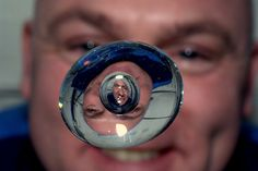 André Kuipers' face in a bubble in a drop of water, aboard the International Space Station.