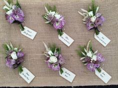 Natural buttonholes to coordinate with a rustic garden gathered bridal bouquet. Lilac delphiniums, purple astrantia, thlaspi, astilbe and cream spray roses tied with aubergine ribbon. Presented on hessian with individual name tags on brown luggage labels.