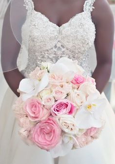 Bride in jewel bodice wedding dress holding pink rose white orchid bridal…