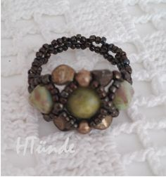 Hugs and Kisses ring in green and brown with pinch beads, seed beads, 6mm pyramid beads and yellow turquoise stone in the middle.