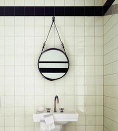 Une idée sympa pour rénover une salle de bain : une carrelage blanc 10X10 avec des joints gris et pour donner à la salle de bain un petit côté rétro, il suffit de peindre une rangée de carrelage en noir tout le long des murs !