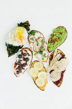 Various toppings for sweet potato toast by Kirsty Begg for Stocksy United avocado, banana, berries, breakfast, clean eating, copy space, cranberry sauce, flat lay, food, food trend, from above, fruit, gluten free, healthy, healthy eating, kale, overhead, peanut butter, poached egg, radish, snack, sweet potato, toast, turkey, vegetable, yam
