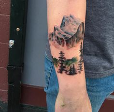 Watercolor mountain range tattoo on forearm by Rachel Ulm