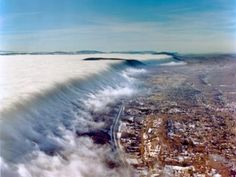 This beautiful aerial photo shows fog rolling over the top of East River Mountain.  The city at the base of the mountain is Bluefield, West Virginia.  The state line separating West Virginia and Virginia runs along the top of the mountain.