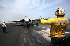 An aircraft director guides an F/A-18E Super Hornet assigned to the Pukin Dogs of Strike Fighter Squadron (VFA) 143 onto a catapult on the flight deck of the aircraft carrier USS Dwight D. Eisenhower (CVN 69).