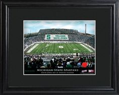 College Stadium Print with Wood Frame - Michingan State. Proclaim him/her the star of the show with our personalized College Stadium print. Each print features the image of a beloved college sports venue, with the crowds in the stands paying clever homage to your favorite sports fan via a personalized message. The text at the bottom also includes the name of the recipient and proclaims an official day in his or her honor. Framed in black, it's a handsome addition to any wall. Makes an ideal…