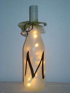 Maybe we all should start drinking wine to save bottles for wedding decor!!! LOL!! - etched/painted bottle with lights inside