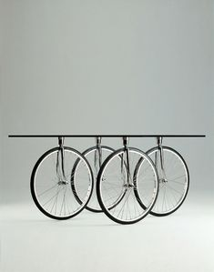 Bicycle wheel table. 15mm float ground glass top.  Wheels fixed to top by stainless steel plates. Inspiring site. Stylepark.com.