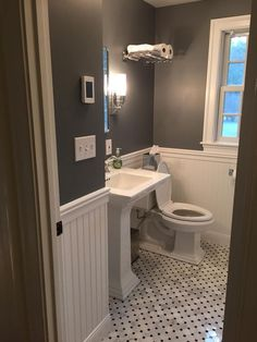 Tiny bathroom remodel. Paint is Rock Gray by Benjamin Moore. Tile is Hampton Hermosa set on the diagonal. Sconces, medicine cabinet, sink fixtures, and train rack all Pottery Barn. Sink and toilet are Kohler.