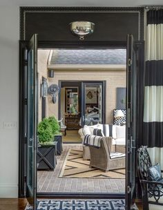 Joy Tribout Interior Design. French doors open on to a courtyard with topiary and outdoor seating.