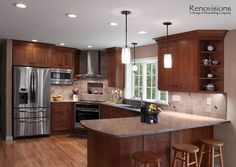 Kitchen remodel by Renovisions. Induction cooktop, stainless steel appliances, cherry cabinets, shaker cabinets, under cabinet lights, tuscan-clay-look porcelain tile backsplash, quartz countertop, peninsula, corner open cabinets, hardwood flooring, pendant lights, recessed lights, corner stove.