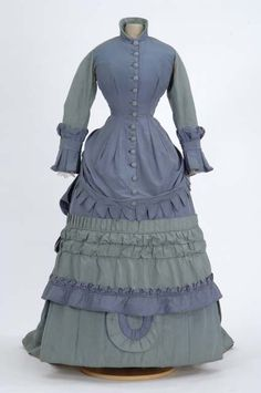 Two toned blue and teal taffeta bustled and trained silk gown. One-piece dress with apron draped bodice with center front self-button closure, Sleeves are full length, two-piece coat sleeves with box pleated cuffs. Hem of bodice apron is Van Dyked (dagged). Attributed to Mrs. Adam Worley, Saint Paul, Minnesota dressmaker, circa 1875.