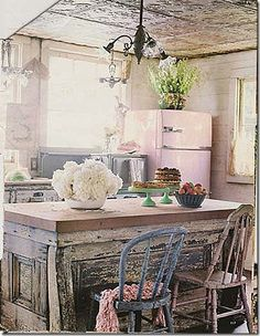 I like that there are pops of color in this kitchen with the jadite cake plates, pink fridge and blue chair. A funky mix with an old feel. I also like the two chandeliers in the kitchen and the tin ceiling.