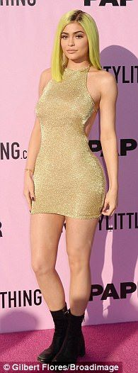 Hands on her hips: Kylie Jenner had difficulty keeping her PrettyLittleThing 'Charlay' gold mini-dress from riding up at the brand's bash in Palm Springs on Friday