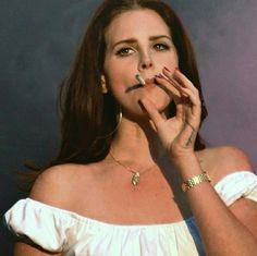 Lana Del Rey smoking a cigarette while performing (Cola)
