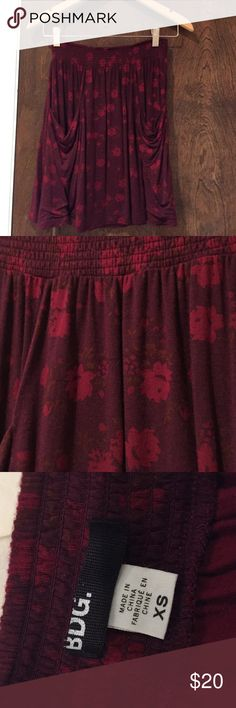 BDG Maroon Floral Skirt This skirt feels like a tee shirt! It is so soft with a stretchy band. Originally purchased from Urban Outfitters and only wore it a few times. I'm 5'2 and it falls right above my knee if I wear it at my waist. It's an XS but I am sure it would fit a small or even a medium. BDG Skirts Mini