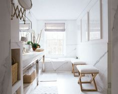 Chic bathroom design with white modern bathroom with marble tiles floors, backsplash and counter tops, polished chrome bathroom vanity, gray silk roman shades, white bathroom rugs, baskets, silver mirror and wood stools.