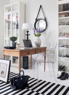 Begagnat skrivbord, stol Louis Ghost av Philippe Starck. Spegel av Jacques Adnet från Gubi. Vas och lampa Tine K. Billybokhyllor och handvävd matta i design av Anna Sörensson för Ikea.